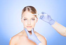 Doctor injecting in a beautiful face of a young woman. Plastic s Stock Photography