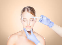 Doctor injecting in a beautiful face of a young woman. Plastic s Royalty Free Stock Image