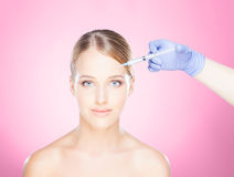 Doctor injecting in a beautiful face of a young woman. Plastic s Royalty Free Stock Photos
