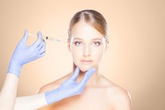 Doctor injecting in a beautiful face of a young woman. Plastic s. Urgery concept stock image