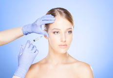 Doctor injecting in a beautiful face of a young woman. Plastic s. Urgery concept stock images