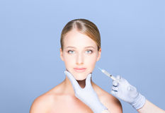 Doctor injecting botox in a beautiful face of a young woman. Pla Royalty Free Stock Photography