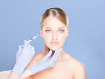 Doctor injecting botox in a beautiful face of a young woman. Pla Stock Photos