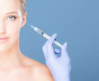 Doctor injecting botox in a beautiful face of a young woman. Pla Stock Images