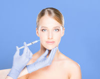 Doctor injecting botox in a beautiful face of a young woman. Pla Stock Image