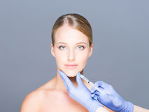 Doctor injecting botox in a beautiful face of a young woman Royalty Free Stock Images