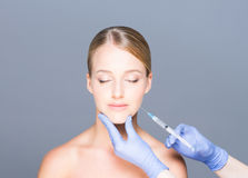 Doctor injecting botox in a beautiful face of a young woman Stock Photo
