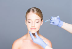 Doctor injecting botox in a beautiful face of a young woman Royalty Free Stock Image