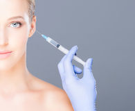 Doctor injecting botox in a beautiful face of a young woman Stock Image