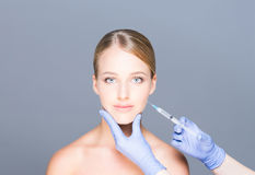 Doctor injecting botox into face of a young woman Stock Photos