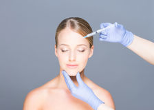 Doctor injecting botox into face of a young woman Royalty Free Stock Images