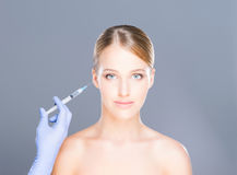 Doctor injecting botox into face of a young woman Stock Photography
