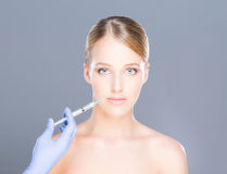 Doctor injecting botox into face of a young woman Stock Image