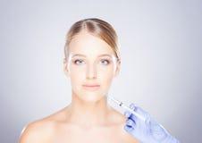 Doctor injecting botox into a woman's face Stock Photos