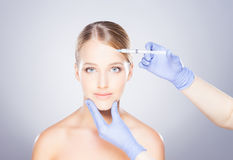 Doctor injecting botox into a woman's face Royalty Free Stock Image
