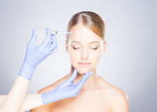 Doctor injecting botox into a woman's face Stock Images