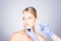 Doctor injecting botox into a woman's face Royalty Free Stock Photography