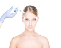 Doctor injecting botox into a woman's face Royalty Free Stock Images