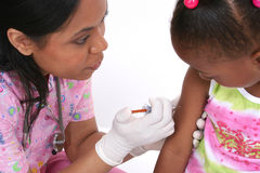 Doctor injecting child. Close up of black female doctor injecting young child in arm royalty free stock photography