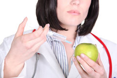 Doctor injecting drugs into apple Royalty Free Stock Image