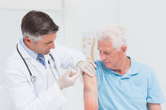 Doctor injecting senior patient in clinic. Male doctor injecting senior patient in clinic stock images