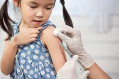 Doctor injecting vaccination in arm of asian little child girl. Healthy and medical concept royalty free stock photography