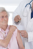 Doctor injecting vaccine to woman Stock Photos
