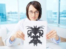 Doctor with inkblot. Serious psychologist showing paper with Rorschach inkblot Stock Photography