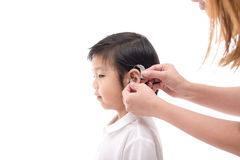 Doctor Inserting Hearing Aid. In the ear of a boy Stock Photography