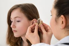 Doctor Inserting Hearing Aid In The Ear Of A Girl. Close-up Of Doctor Inserting Hearing Aid In The Ear Of A Girl stock photos