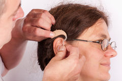 Doctor inserting a hearing aid. Into the ear of a women patient Stock Photography
