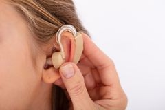 Doctor Inserting Hearing Aid In Girl`s Ear. Close-up Of A Doctor Hand Inserting Hearing Aid In Girl`s Ear stock photo
