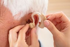 Doctor Inserting Hearing Aid In Patient`s Ear. Female Doctor`s Hand Inserting Hearing Aid In Senior Male Patient`s Ear royalty free stock photography