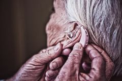 Doctor inserting hearing aid in senior patient ear. In hospital, Close-up royalty free stock photos