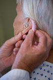 Doctor inserting hearing aid in senior patient ear Stock Photo