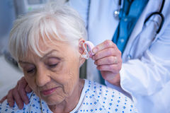 Doctor inserting hearing aid in senior patient ear Royalty Free Stock Photo