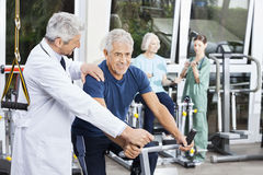 Doctor Instructing Senior Man On Exercise Bike At Fitness Center. Mature male doctor instructing senior men on exercise bike at fitness center Stock Images