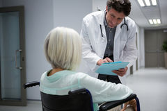 Doctor interacting with patient sitting on wheelchair in corridor royalty free stock images