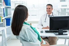 Doctor interacting with a pregnant woman at clinic Stock Image