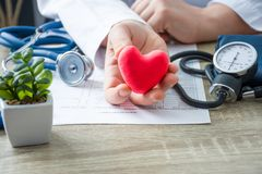 Doctor of internal medicine and cardiologist holding in his hands and shows to patient figure of red card heart during medical con royalty free stock photography