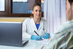 Doctor interview a patient in the medical consultation. Physician noting the patient`s symptoms at the medical office / Doctor interview a patient in the medical Royalty Free Stock Image