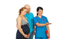 Doctor invite pregnant couple to join Royalty Free Stock Images