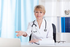 Doctor inviting patient on a chair Stock Image