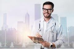 Doctor joven alegre que sonríe mientras que hace notas Imagen de archivo libre de regalías