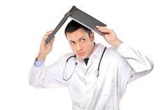 Doctor joven asustado que cubre su cabeza Imagen de archivo libre de regalías