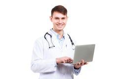 Doctor joven con el ordenador portátil aislado Fotos de archivo