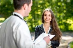 Doctor joven con el paciente joven y bonito de la mujer foto de archivo libre de regalías