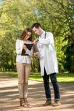 Doctor joven con el paciente joven y bonito de la mujer imagen de archivo libre de regalías