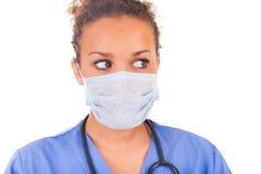 Doctor joven con la máscara y el estetoscopio aislados en el backgro blanco imagenes de archivo