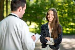 Doctor joven con la mujer joven y bonita fotos de archivo